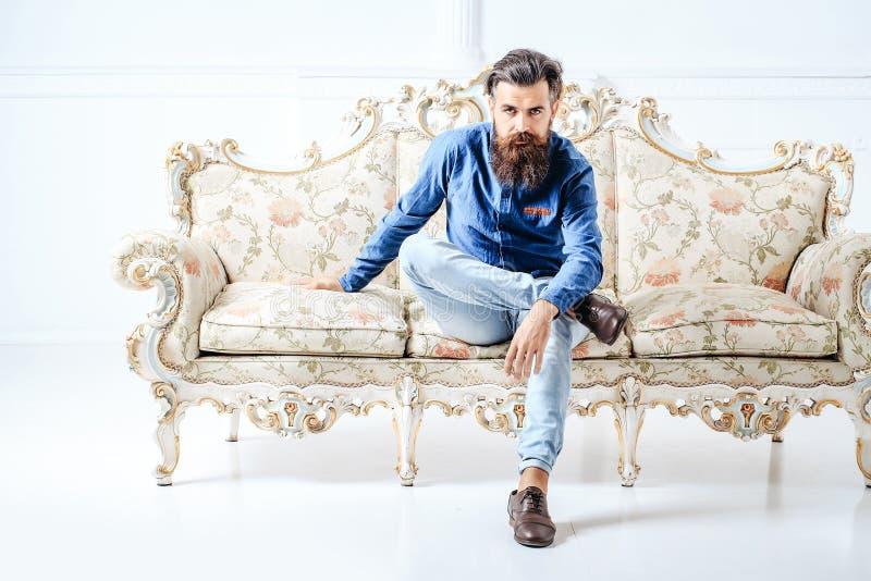 长沙发的英俊的有胡子的人 库存图片