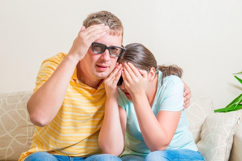 长沙发的观看可怕电影的男人和妇女 图库摄影