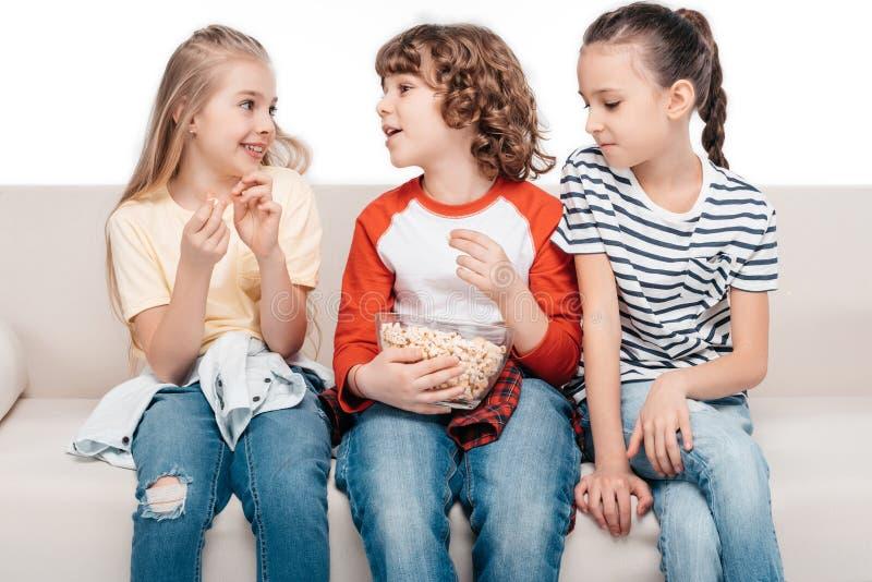 长沙发的逗人喜爱的孩子用玉米花 库存照片