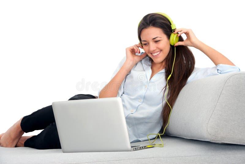 长沙发耳机膝上型计算机妇女年轻人 免版税图库摄影