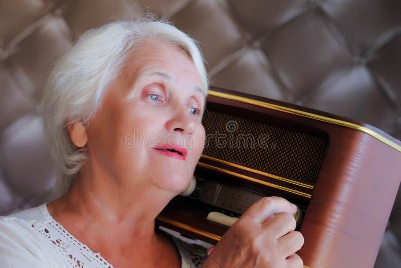 年长灰发的妇女听的葡萄酒收音机 免版税库存照片