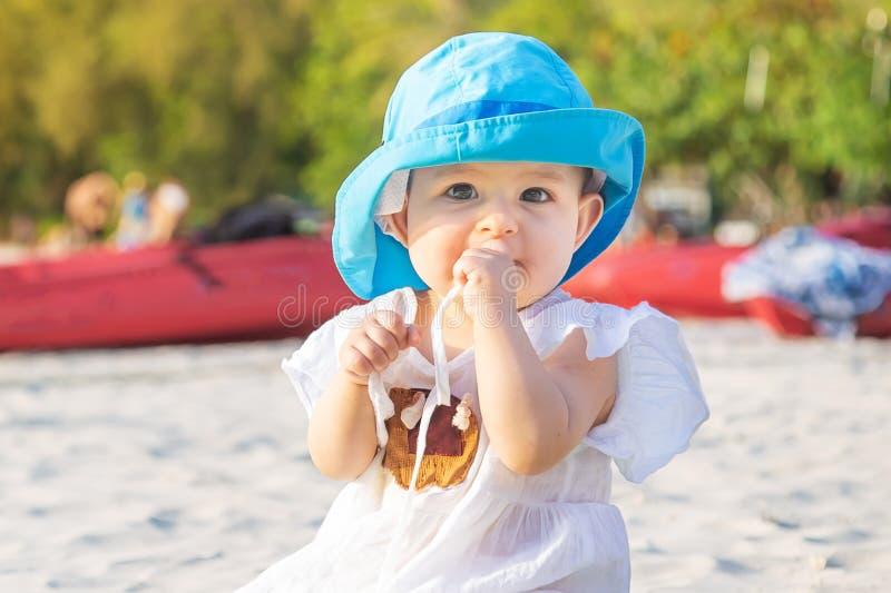 长牙齿在8个月 女婴坐海滩和嚼teether 在蓝色帽子和白色礼服在竹席子 免版税库存照片