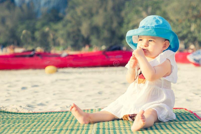 长牙齿在8 mounth 女婴坐海滩和嚼teether 在蓝色帽子和白色礼服在竹席子 图库摄影