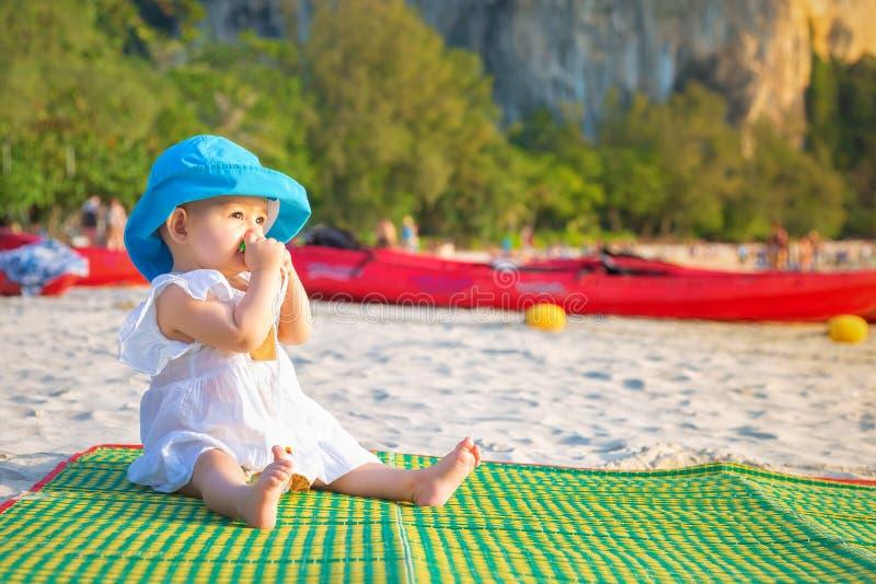 长牙齿在8 mounth 女婴坐海滩和嚼teether 在蓝色帽子和白色礼服在竹席子 免版税库存照片