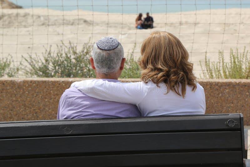 年长犹太夫妇在地中海海滩附近放松 图库摄影