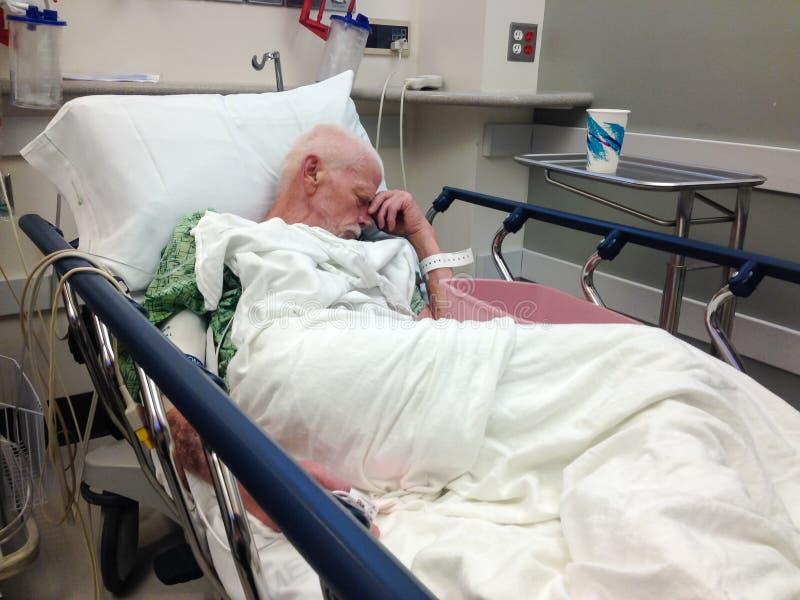 年长男性住院病人在医院病床上 免版税图库摄影