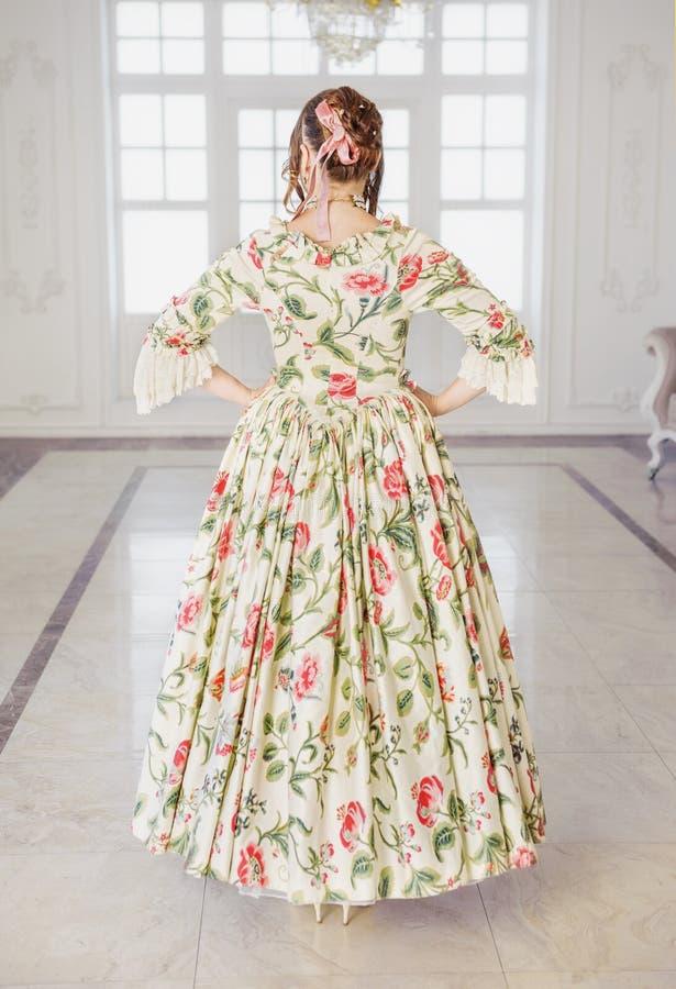 长的中世纪礼服的美丽的妇女在大厅里 后面姿势 库存照片