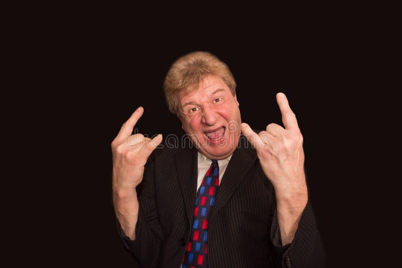 年长的人做垫铁打手势描述重金属的摇滚乐 免版税库存图片