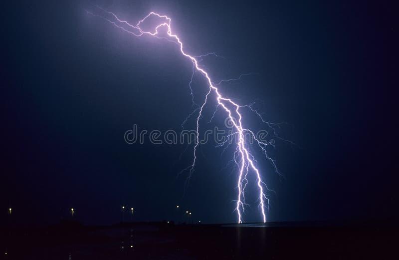长的叉状闪电螺栓从夏天雷暴发生下来在湖艾瑟尔湖,荷兰 免版税图库摄影