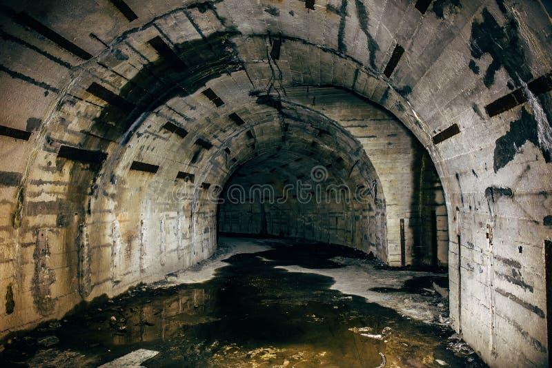 长的地下隧道或走廊在被放弃的苏联军事地堡或地下室或者避难所与蠕动的大气 免版税库存照片