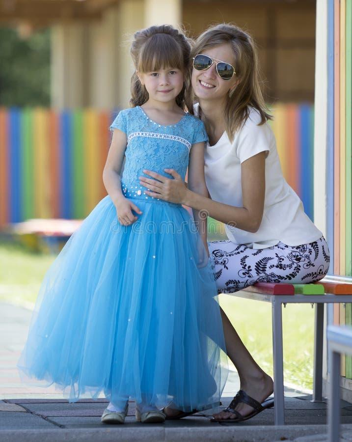 长的好的蓝色晚礼服的年轻亭亭玉立的白肤金发的微笑的母亲、伯母或者姐妹拥抱小俏丽的学龄前女儿女孩  库存照片