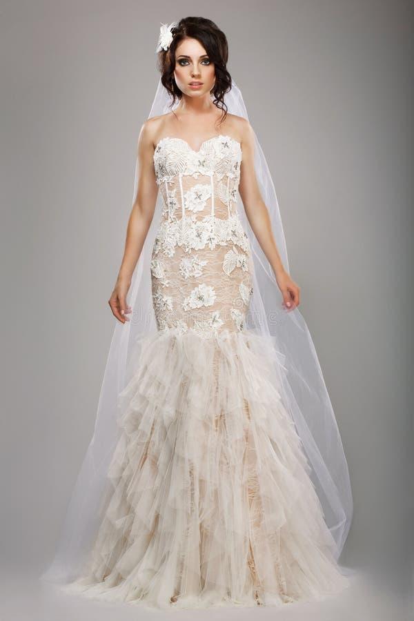 长的婚礼礼服和面纱的时装模特儿优等的新娘 免版税库存图片