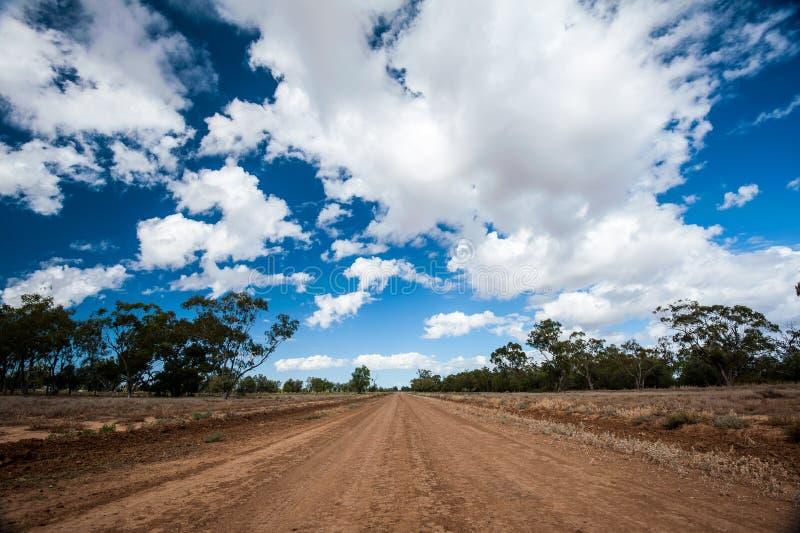 长的平直的红色土路在澳大利亚的澳洲内地 库存图片