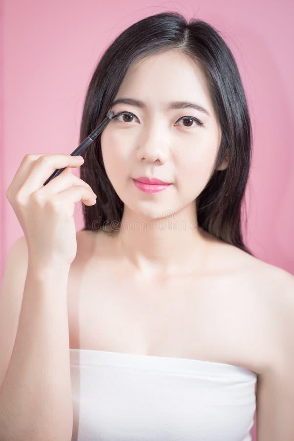 长的应用在光滑的面孔的头发亚裔年轻美丽的妇女化妆粉末刷子被隔绝在桃红色背景 自然的构成 免版税库存图片