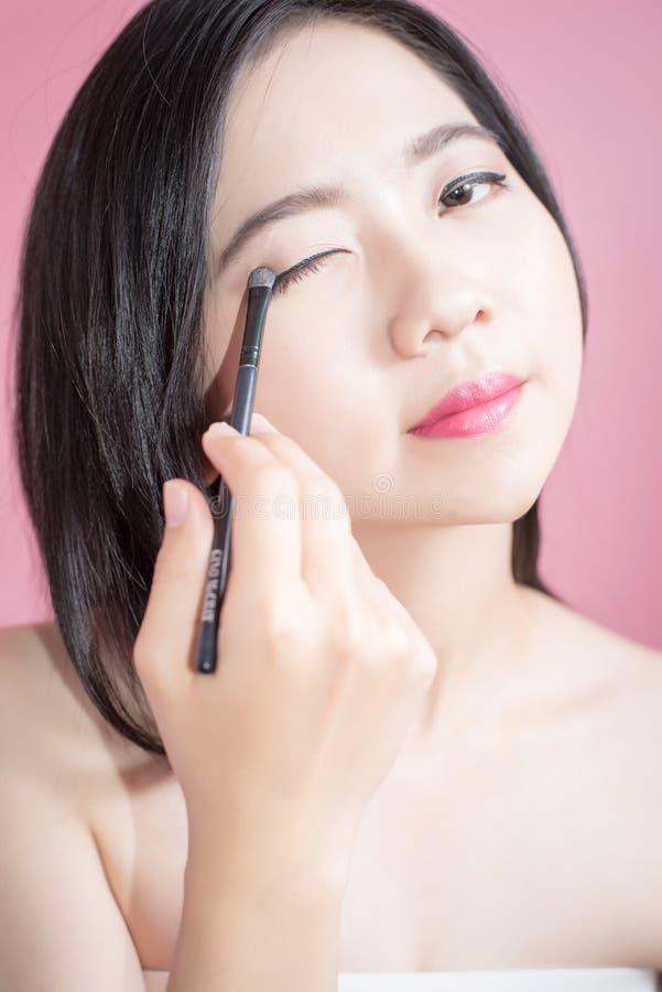 长的应用在光滑的面孔的头发亚裔年轻美丽的妇女化妆粉末刷子被隔绝在桃红色背景 自然 免版税库存图片