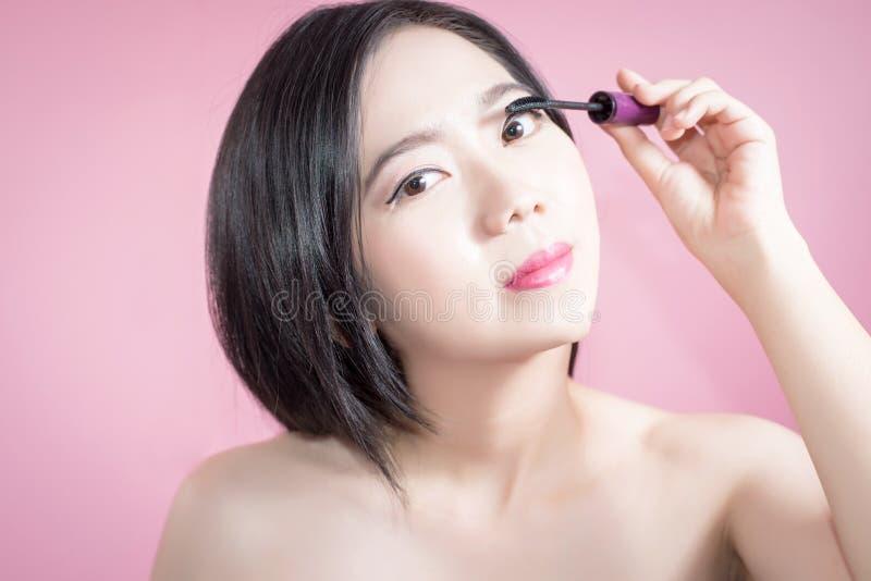 长的应用染睫毛油的头发亚裔年轻美丽的妇女被隔绝在桃红色背景 自然构成,温泉疗法, skincare 图库摄影