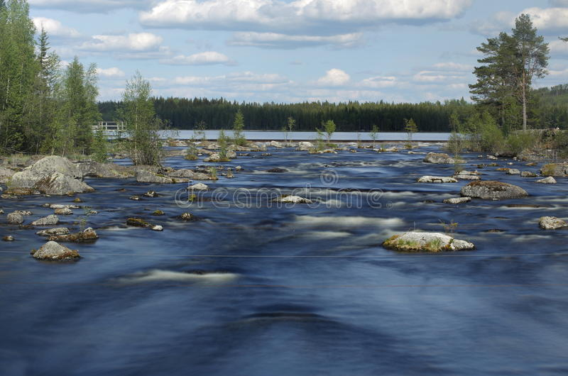 长的曝光射击了在水门前面的急流在瑞典河在Jaemtland 免版税图库摄影