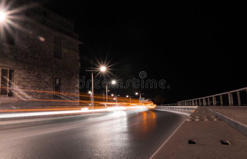 长的曝光橙色颜色转移了汽车光足迹城市街道低角度 库存图片
