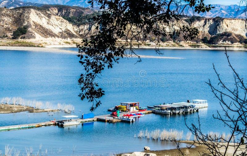 长的木码头和小船在加利福尼亚` s湖Cachuma有圣拉斐尔山的 库存照片