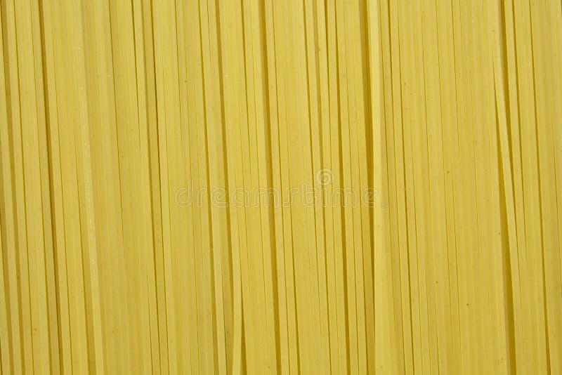 长的未加工的黄色意粉面团背景  免版税库存照片