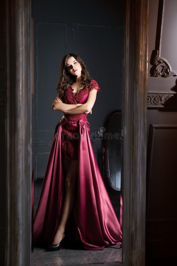 长的深紫红色鞋带礼服的可爱的妇女 反映在镜子 免版税库存图片
