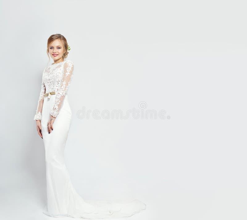 长的白色婚礼礼服的新娘在白色背景 在妇女` s身体的豪华礼服 女孩准备结婚 免版税库存照片