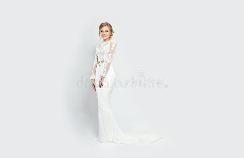 长的白色婚礼礼服的新娘妇女在白色背景 L 免版税图库摄影