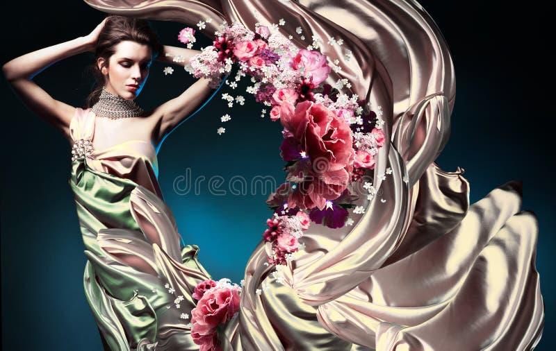 长的礼服和花的美丽的妇女 免版税库存照片