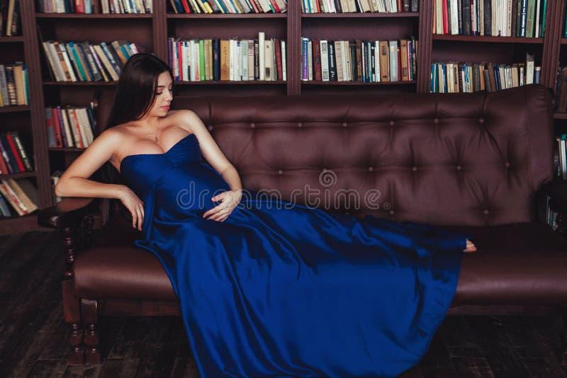 长的礼服的好看起来的孕妇 愉快的怀孕的概念 免版税库存图片