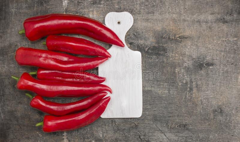 长的红色新鲜的胡椒,在白色切板的辣椒粉 免版税库存照片