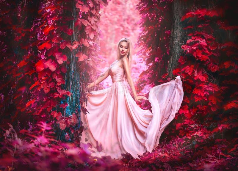 长的薄绸的礼服的秀丽浪漫年轻女人有摆在幻想有薄雾的森林美丽的愉快的新娘式样女孩的褂子的 免版税库存图片