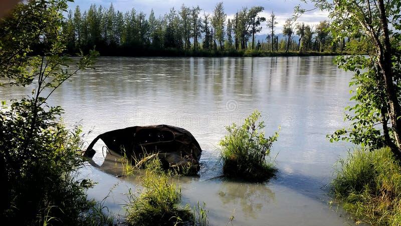 长的被放弃的车在河 库存图片
