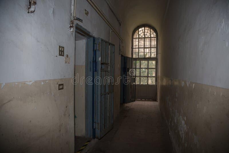 长的走廊和监狱的白色和破旧的墙壁 免版税库存照片