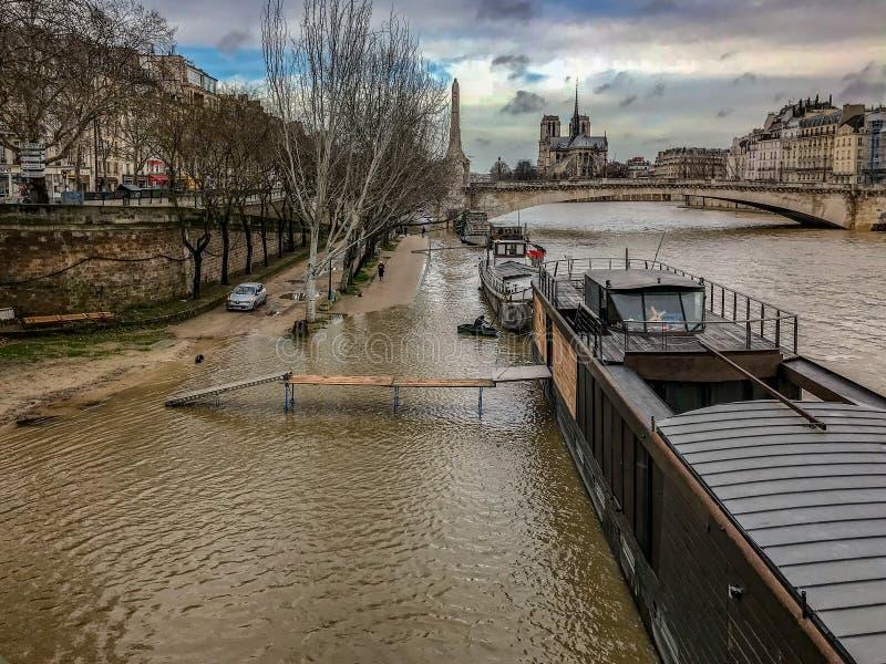 长的跳板从居住船几乎舒展对被充斥的塞纳河的岸在巴黎,法国 免版税库存照片