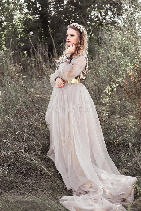 长的金黄礼服的年轻美丽的女孩有圈的,与花花圈在她的头的在春天绿色庭院里 库存照片