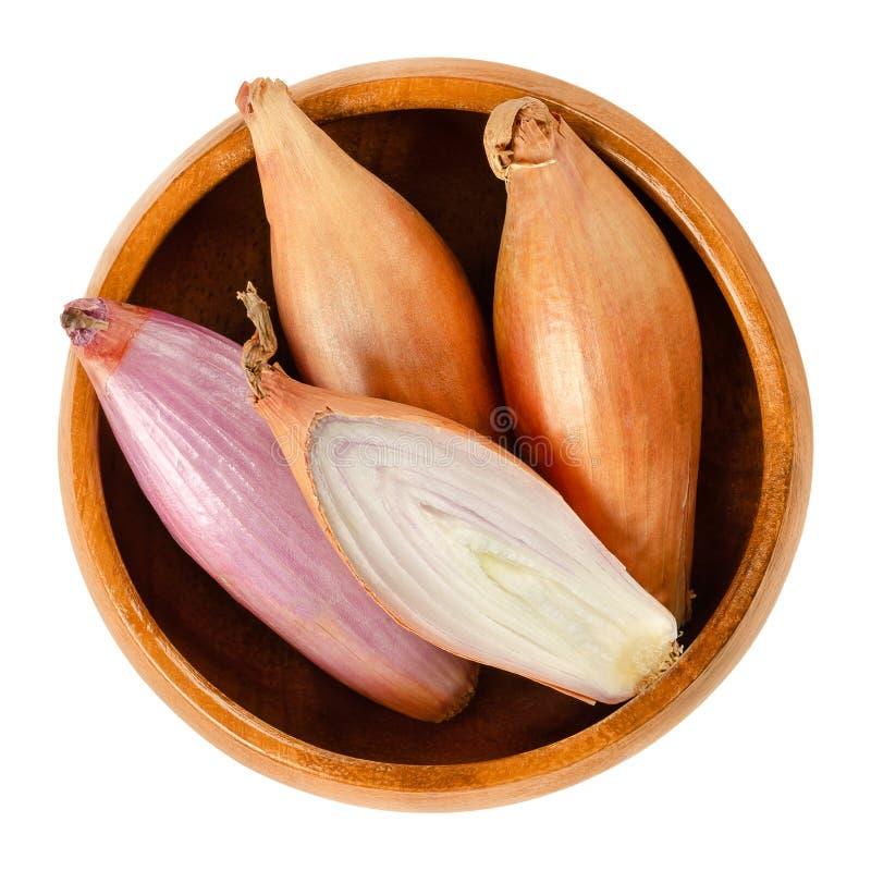 长的青葱,整个和切,在白色的木碗 库存图片