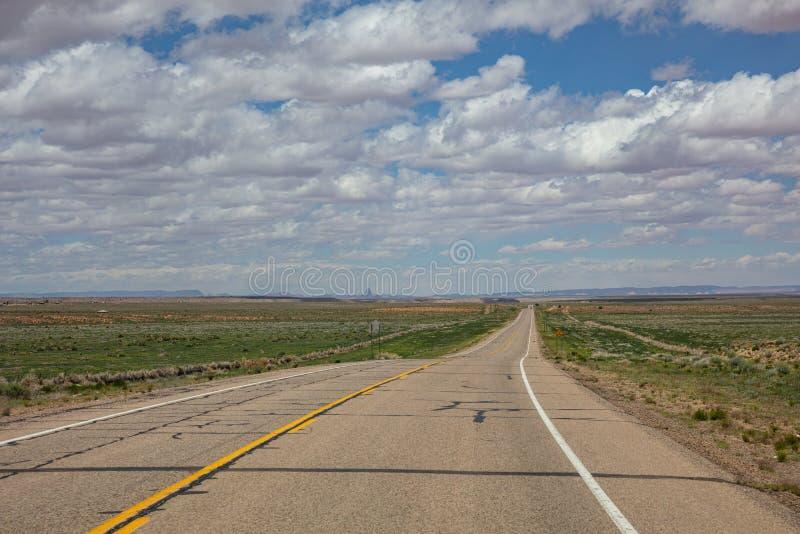 长的高速公路,多云天空蔚蓝 纪念碑谷那瓦伙族人国家,亚利桑那犹他美国 免版税库存图片