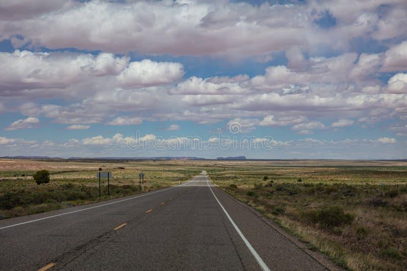 长的高速公路,多云天空蔚蓝 纪念碑谷那瓦伙族人国家,亚利桑那犹他美国 图库摄影