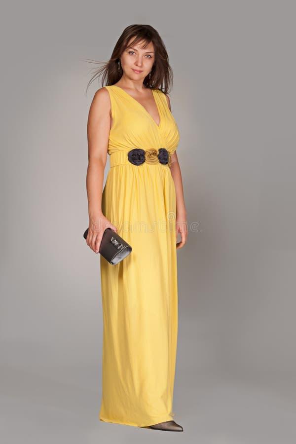 长的黄色礼服的美丽的时髦的女人。 库存照片