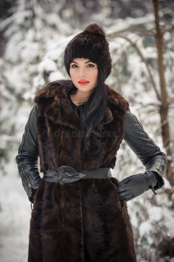 长的黑毛皮大衣和盖帽的美女享受在森林深色女孩摆在的冬天风景 免版税图库摄影