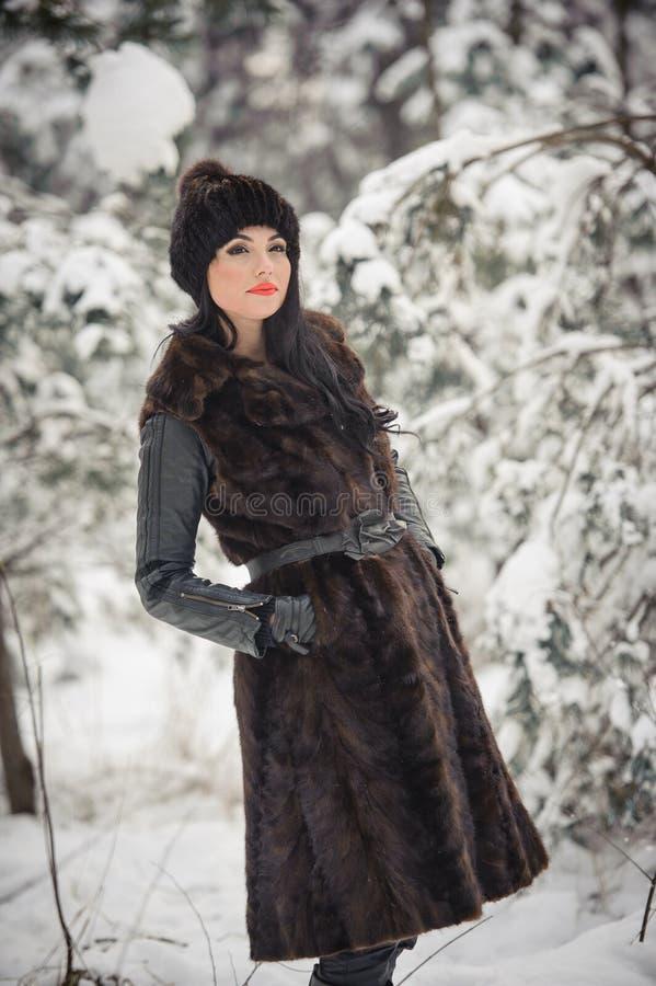 长的黑毛皮大衣和盖帽的美女享受在森林深色女孩摆在的冬天风景 免版税库存图片