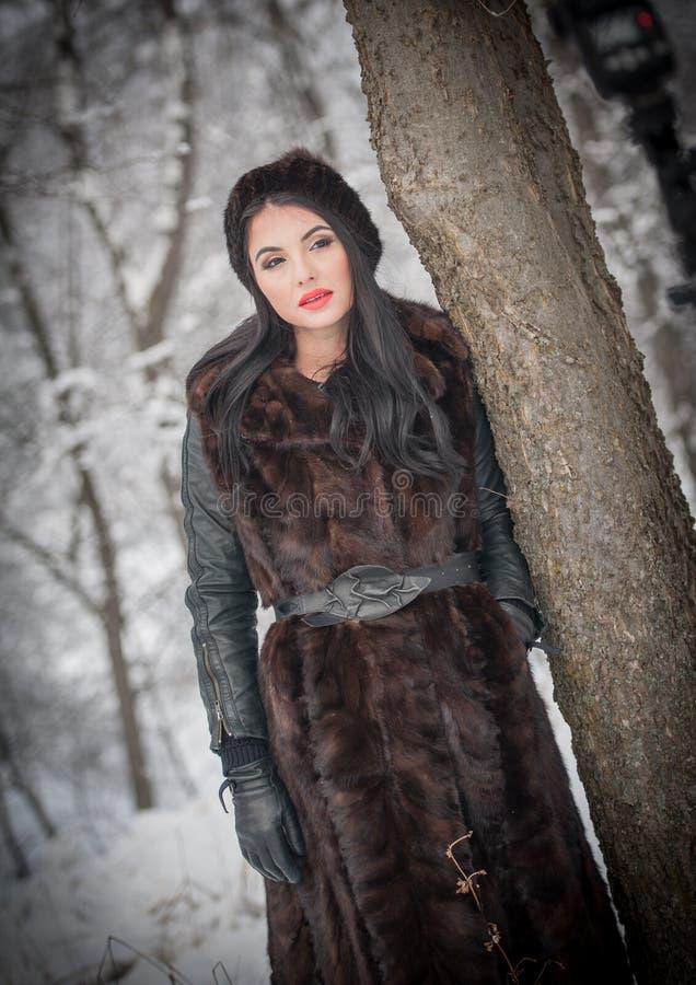 长的黑毛皮大衣和盖帽的美女享受在森林深色女孩摆在的冬天风景 免版税库存照片
