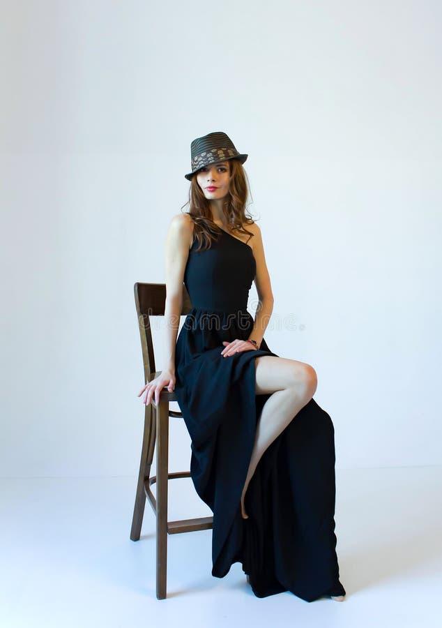 长的黑礼服和帽子的少妇,坐在白色背景的椅子 库存照片