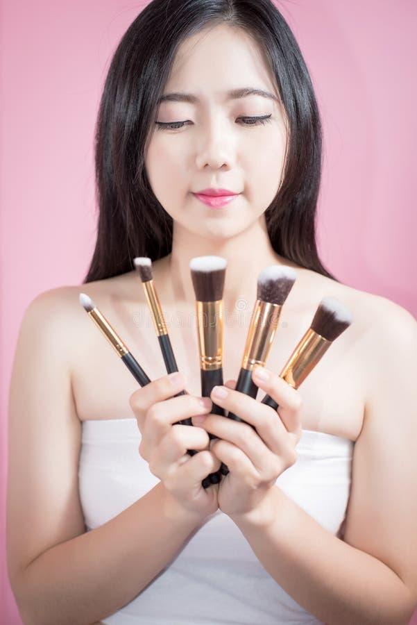 长的头发亚洲年轻美好的妇女微笑和乐趣,接触她的面孔并且拿着化妆粉末电刷组,被隔绝在桃红色 库存图片
