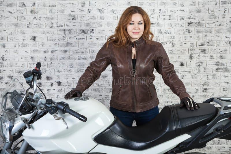 长的头发妇女站立在她的在车库,砖墙背景的街道摩托车附近的motorbiker 图库摄影