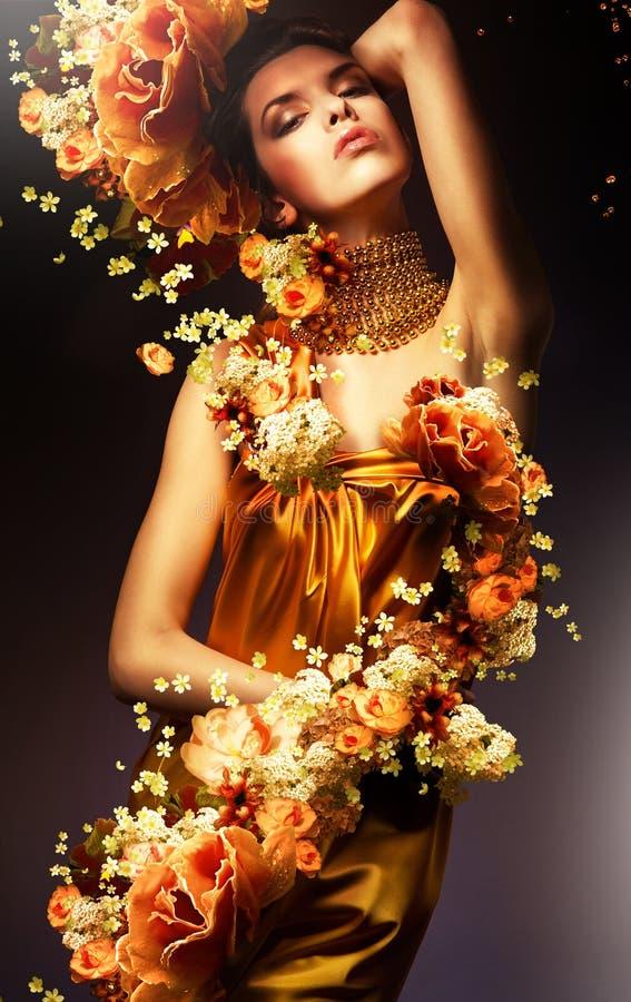 长的黄色礼服的肉欲的妇女 免版税库存图片