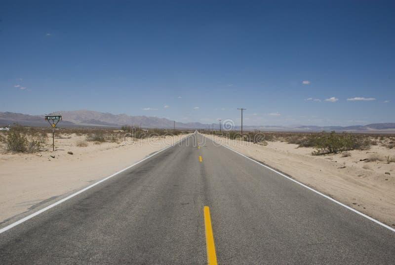 长的直路通过加利福尼亚贫瘠沙漠风景  免版税库存照片