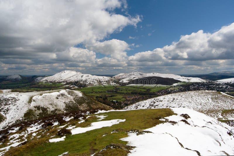 长的Mynd,在拟订的磨房谷的看法和Caer Caradoc,在雪,在萨罗普郡小山的春天下的峰顶的小山 图库摄影