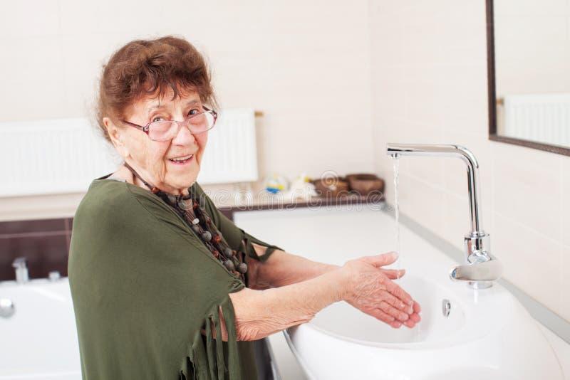 年长老妇人洗她的手 免版税库存照片