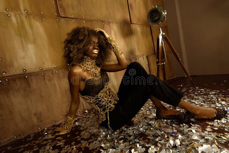 长腿的美好的非裔美国人的魅力式样醒目的性感的姿势坐地板在明亮的演播室 免版税库存照片